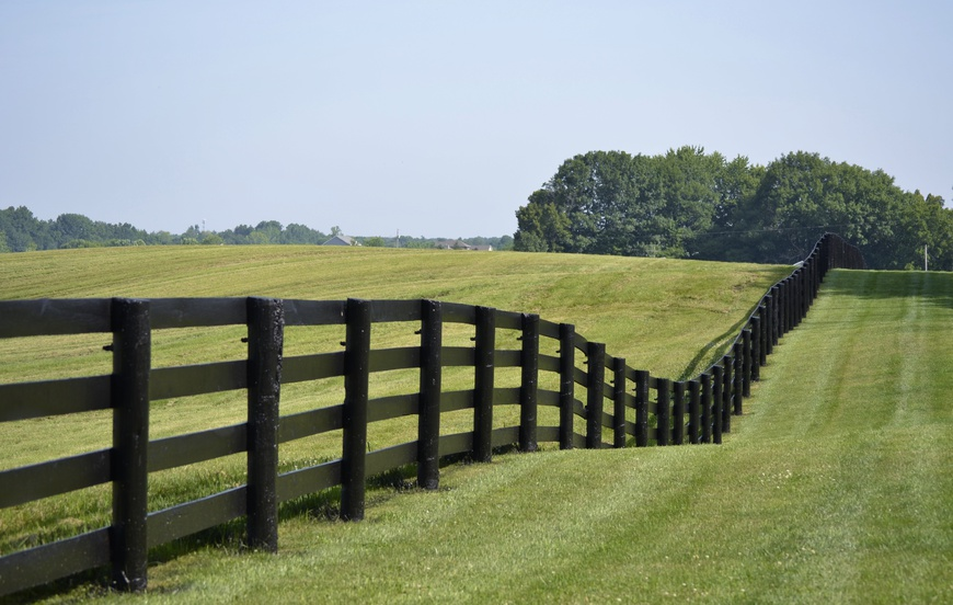 Painted fence dividing pastures and borders on rural property